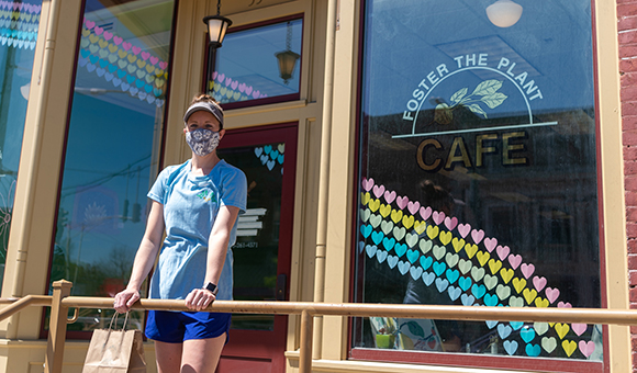 Lynzie Schulte stands in front of her cafe Foster the Plant, wearing a mask.