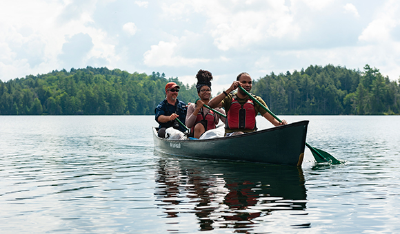 Professor Matt Burnett canoes with two students from the Adirondack Experience class.