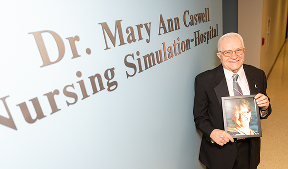 Alson T. Caswell Sr. stands next to the newly unveiled Dr. Mary Ann Caswell Nursing Simulation-Hospital holding a picture of his late wife and the namesake of the new learning area.