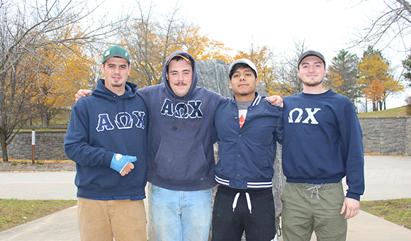 AOX Fraternity poses in front of the Campus Plaza rock.