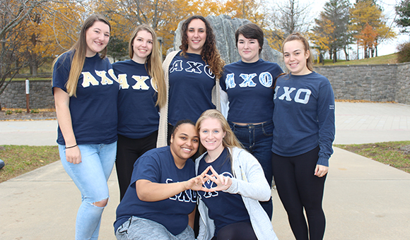 AXO Sorority poses in front of the Campus Plaza rock.