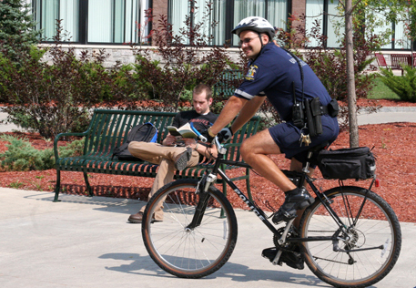 An officer rides a bicycle through the Roselle Plaza.