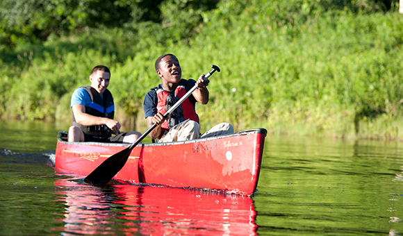 Two students canoe down the Grasse River in a red canoe.
