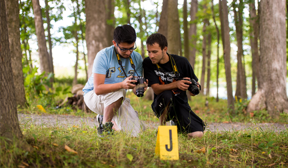 Two students review a photo in the viewfinder at a crime scene.