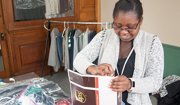 A student packages up professional clothing to send to an online student.