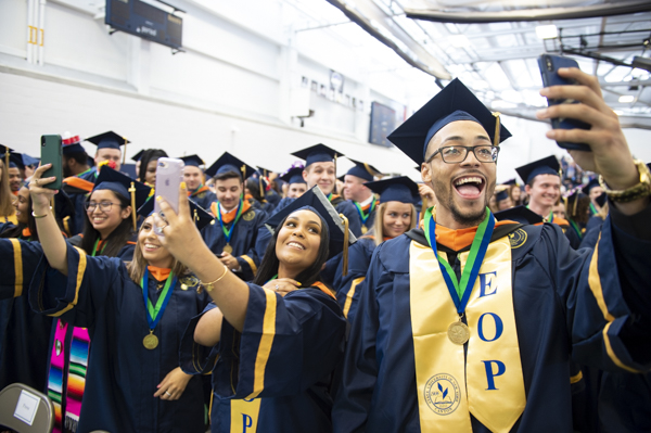 A group of graduates take selfies at SUNY Canton's commencement ceremony