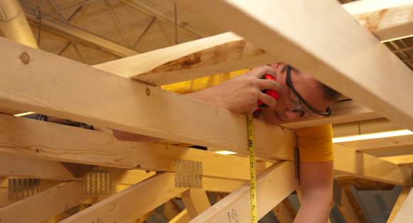 A student measures lumber in the rafters of a mock building.