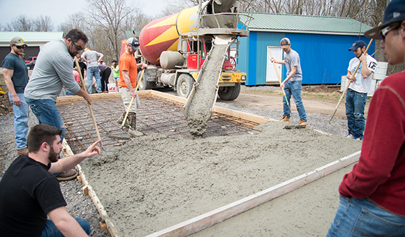 A class pours a concrete pad outside the Physical Plant.