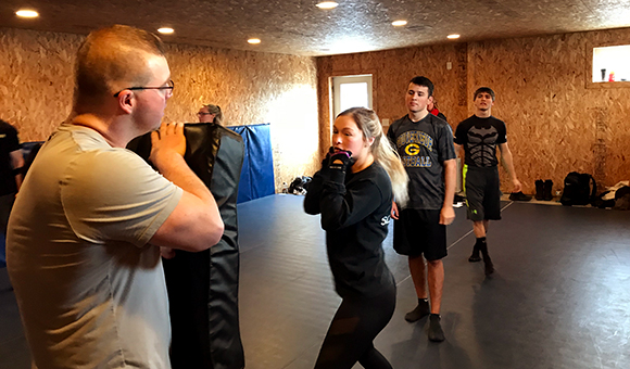 A cadet gets ready to punch a punching bag during a training exercise
