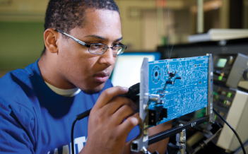 A student solders a motherboard