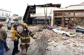 Emergency personnel inspect damage from an earthquake.
