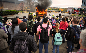 Students watch a mock burn in the campus plaza.