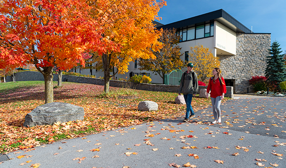 Two students walk outside of Wicks Hall on an autumn day.