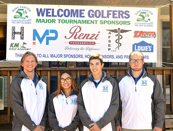 Four students stand in front of the Tee Off Classic Tourney sign.