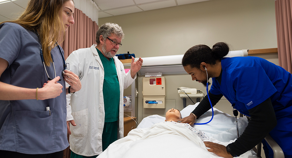 A student checks a patient's heart while another student and instructor look on.
