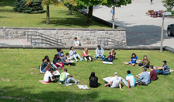 An outdoor class with students sitting in a circle on the grass.