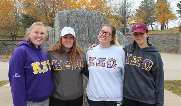 KXO Sorority poses in front of the Campus Plaza rock.