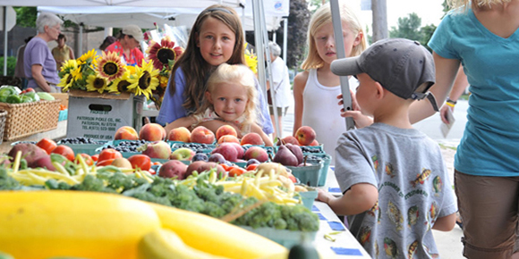 Children check out the fruits and vegetables available at the Canton Farmer's Market in downtown Canton.
