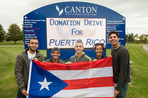 Five students hold a Puerto Rican flag in front of the SUNY Canton digital sign.