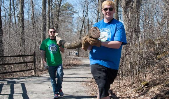 Students carry a log down a path at the Grasse River Heritage Park.