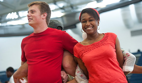 Students have arms interlocked during an orientation exercise.