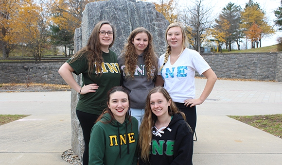 PNE Sorority poses in front of the Campus Plaza rock.