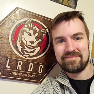 Ryan Hewer poses in front of a Little Red Dog Gaming logo
