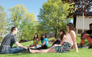 A professor leads an outdoor class while students sit on the lawn,