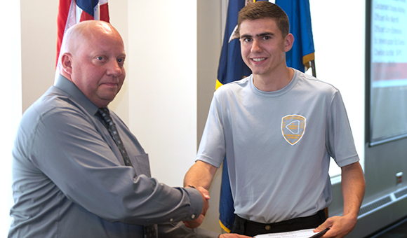 Rodney Votra shakes hands with cadet Jesse Walley at the Corrections graduation ceremony.
