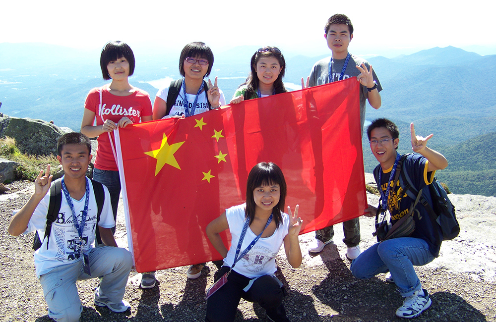 Chinese students hold a flag on top of Whiteface Mountain