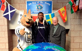 Roody, President Szafran and a student pose for a photo in front of a giant globe.