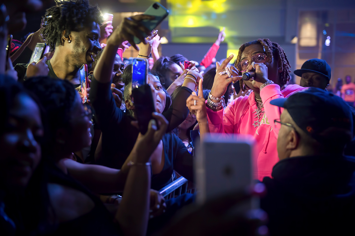 Gunna performs at Roos House while students snap photos.
