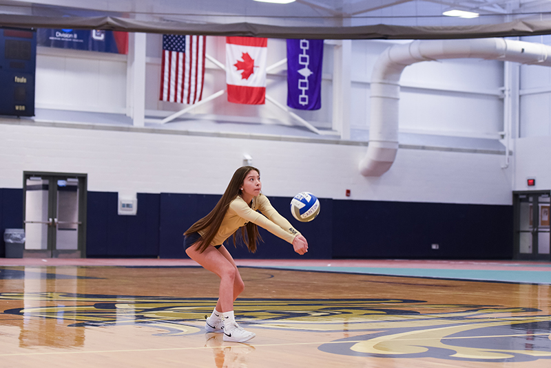 Tatum LaFrance sets a volleyball with the Iroquois flag in the background