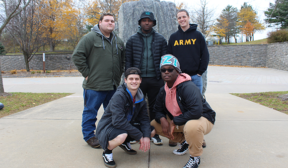 YZI Fraternity poses in front of the Campus Plaza rock.